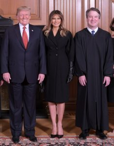 President Trump, First Lady Melania Trump, and Justice Brett Kavanaugh, standing together in a formal setting.