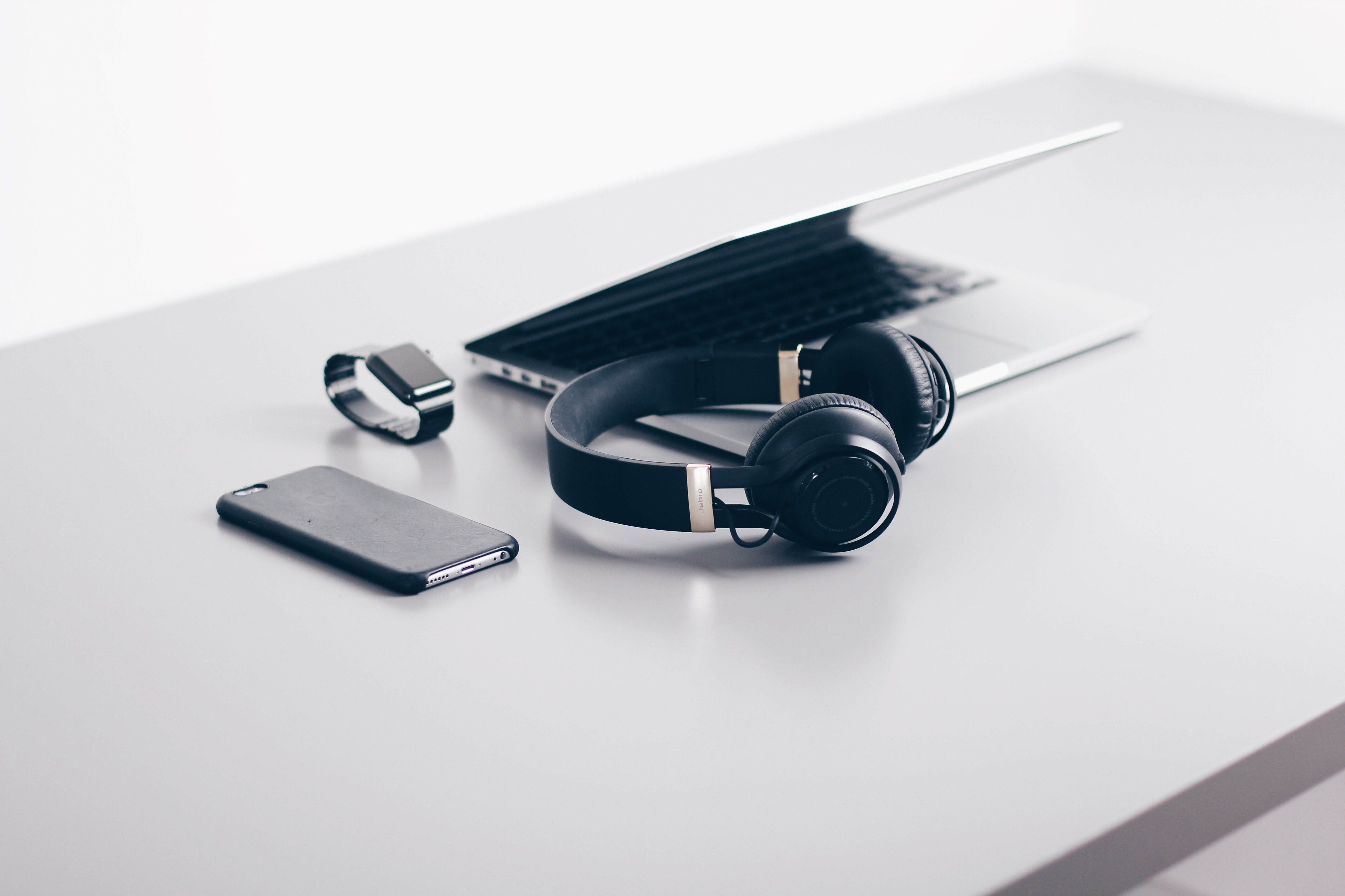 Black cordless headphones beside closed black laptop computer and smartphone; image by Christopher Gower, via Unsplash.com.