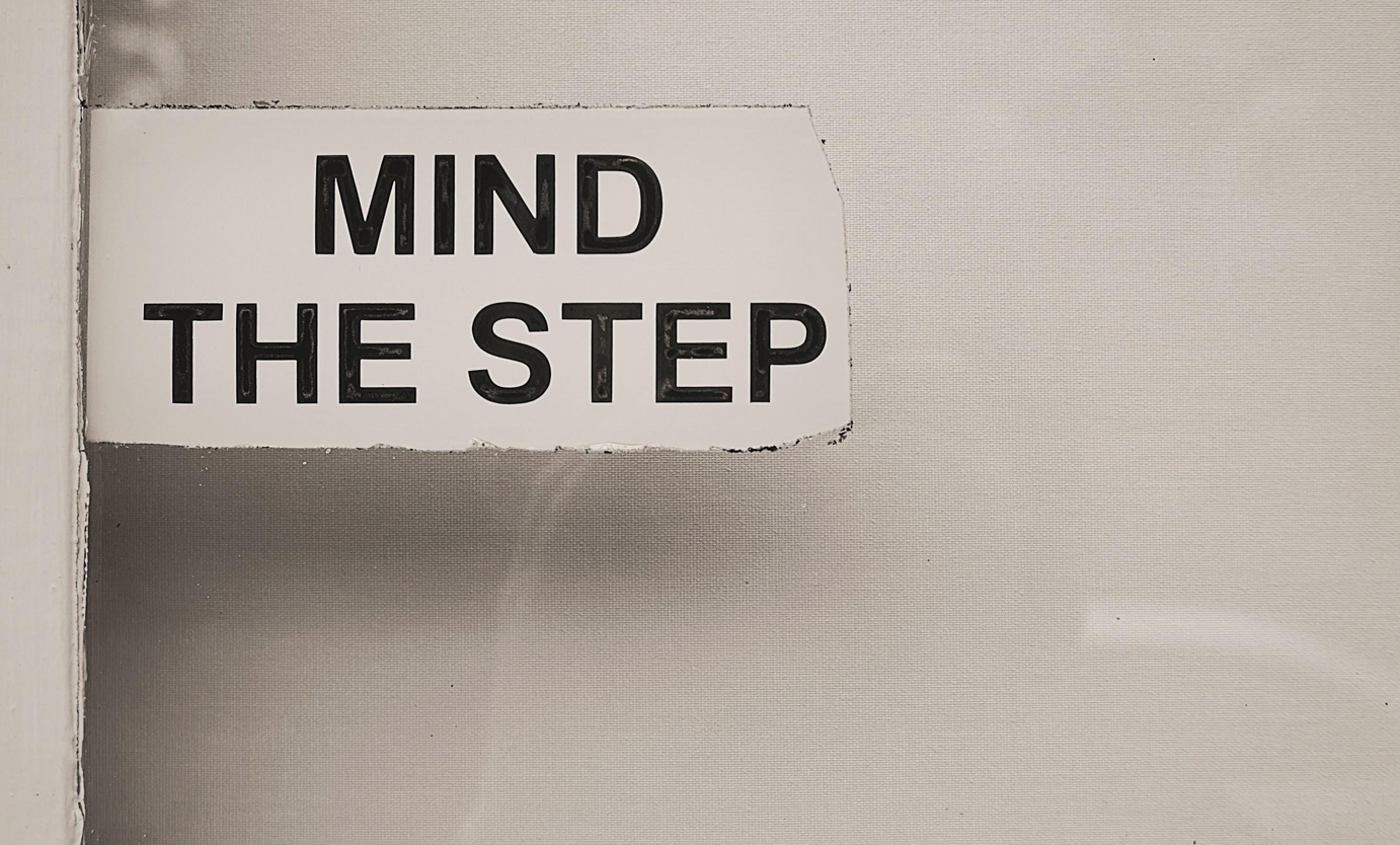 "White sign with black lettering that reads, ""Mind the step."" Image by Jason Dent, via Unsplash.com."