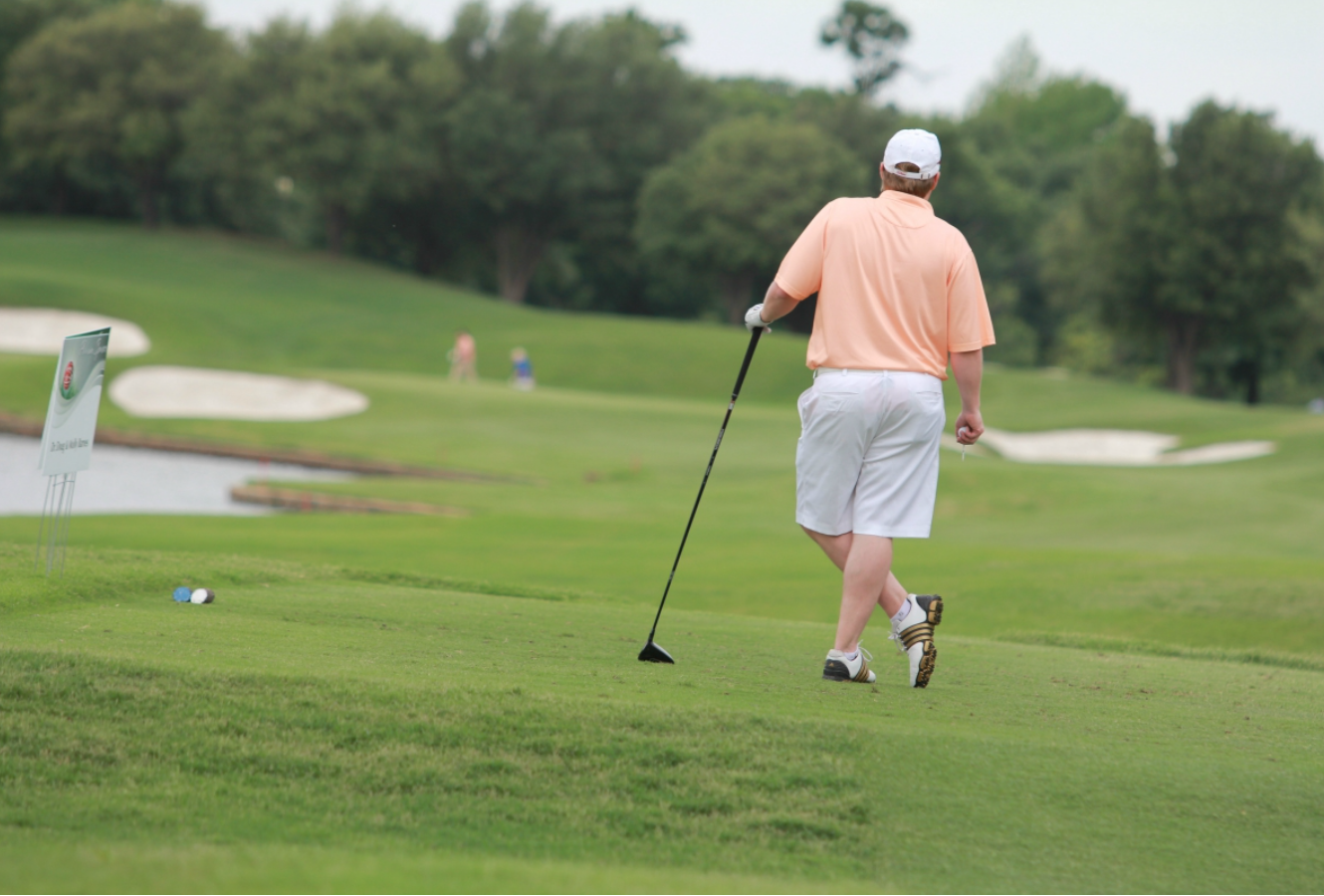 Man on golf course, leaning on golf club; image by Hal Gatewood, via Unsplash.com.