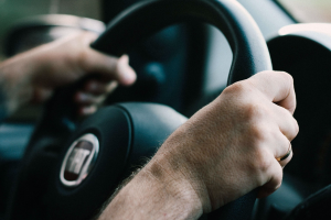 Man's hands on steering wheel; image by Matheus Ferrero, via Unsplash.com.