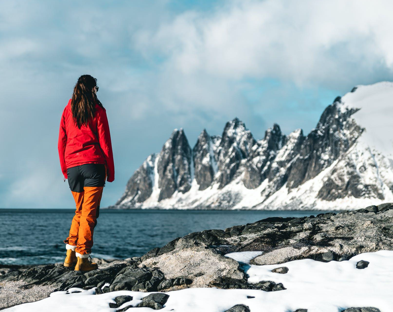 Woman standing by beach in winter; image by Tobias Bjørkli, via Pexels.com.
