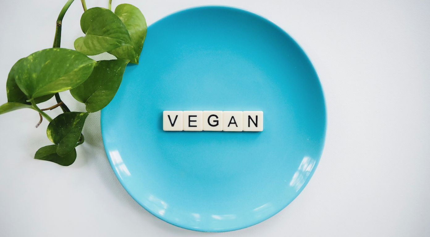 "White surface, green plant, blue plate with ""Vegan"" on it in lettered tiles; image by Vegan Liftz, via Unsplash.com."