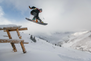 Man going over ramp on a snowboard; image by Visit Almaty, via Pexels.com.