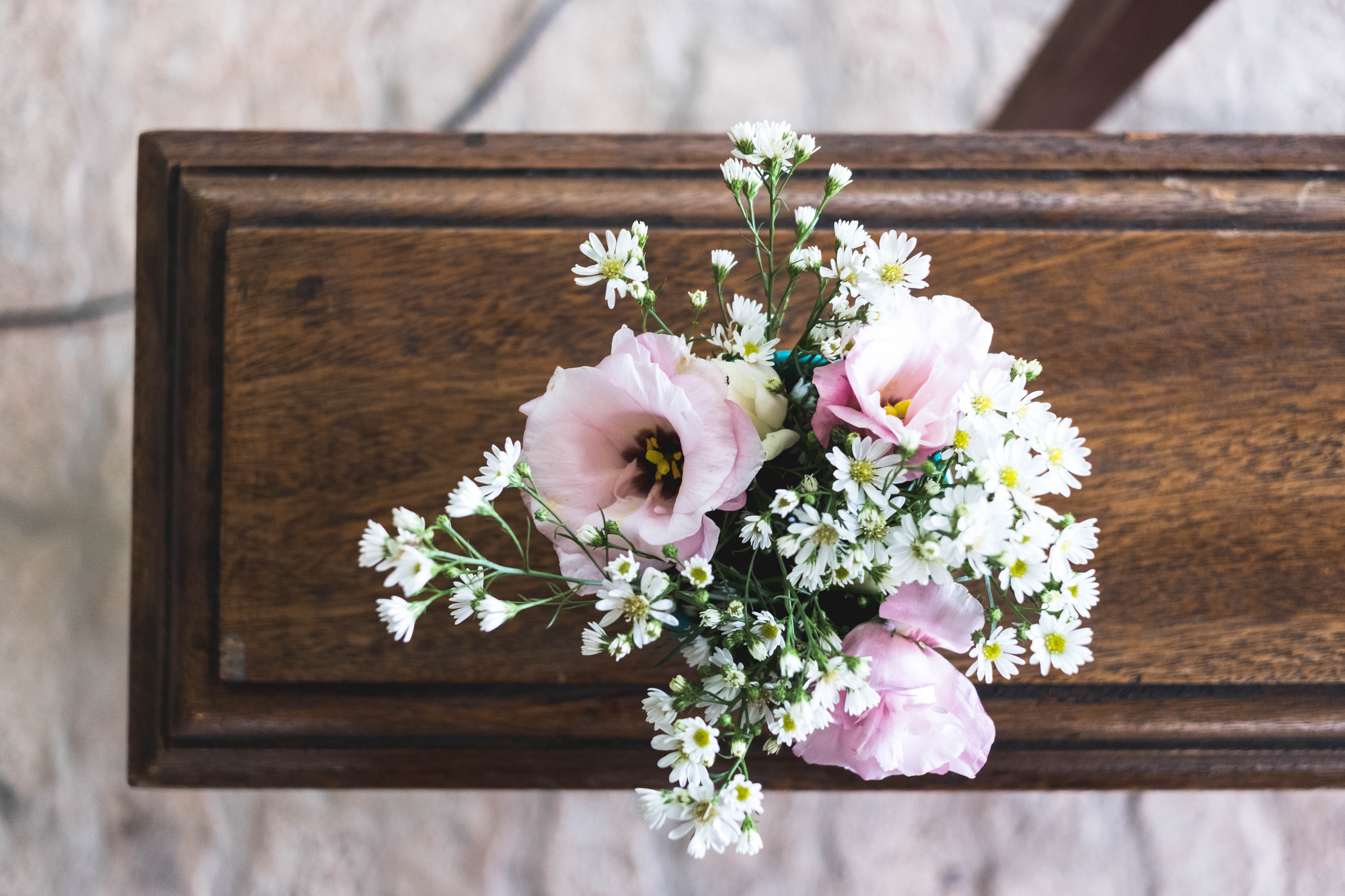 Pink and white flowers on a plain wooden casket; image by Mayron Oliveira, via Unsplash.com.