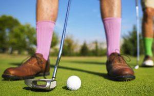 Man in lavender socks preparing golf shot; image by Morgan David de Lossy, via Unsplash.com.