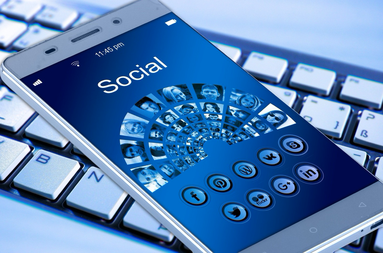 "Smartphone with ""Social"" on the screen & various social media icons, sitting on computer keyboard; image by Geralt, via Unsplash.com."