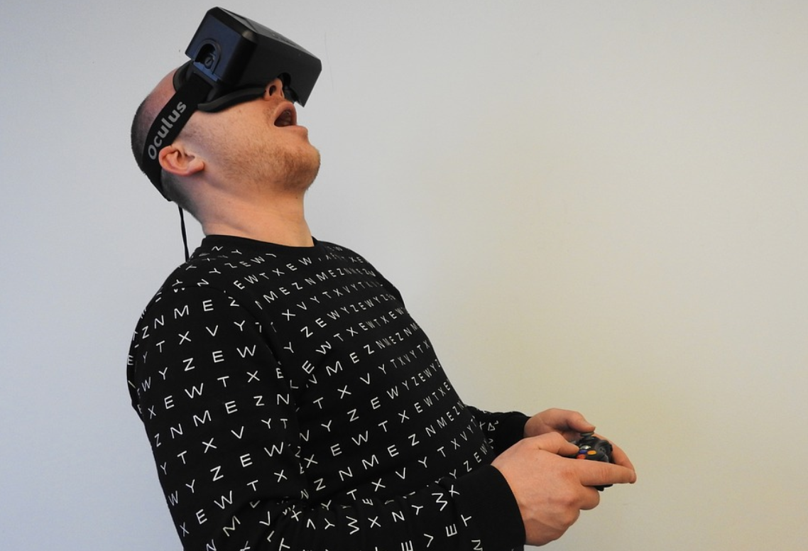 Man in black and white shirt wearing a VR headset and playing a game; image by Hammer and Tusk, via Pixabay.com.