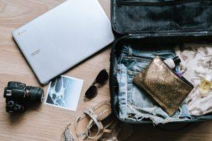 Suitcase with clothing, camera, laptop; image by Anete Lūsiņa, via Unsplash.com.
