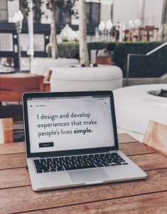 "Laptop with screen saying, ""I design and develop experiences that make people's lives simple."" Image by Ben Kolde, via Unsplash.com."