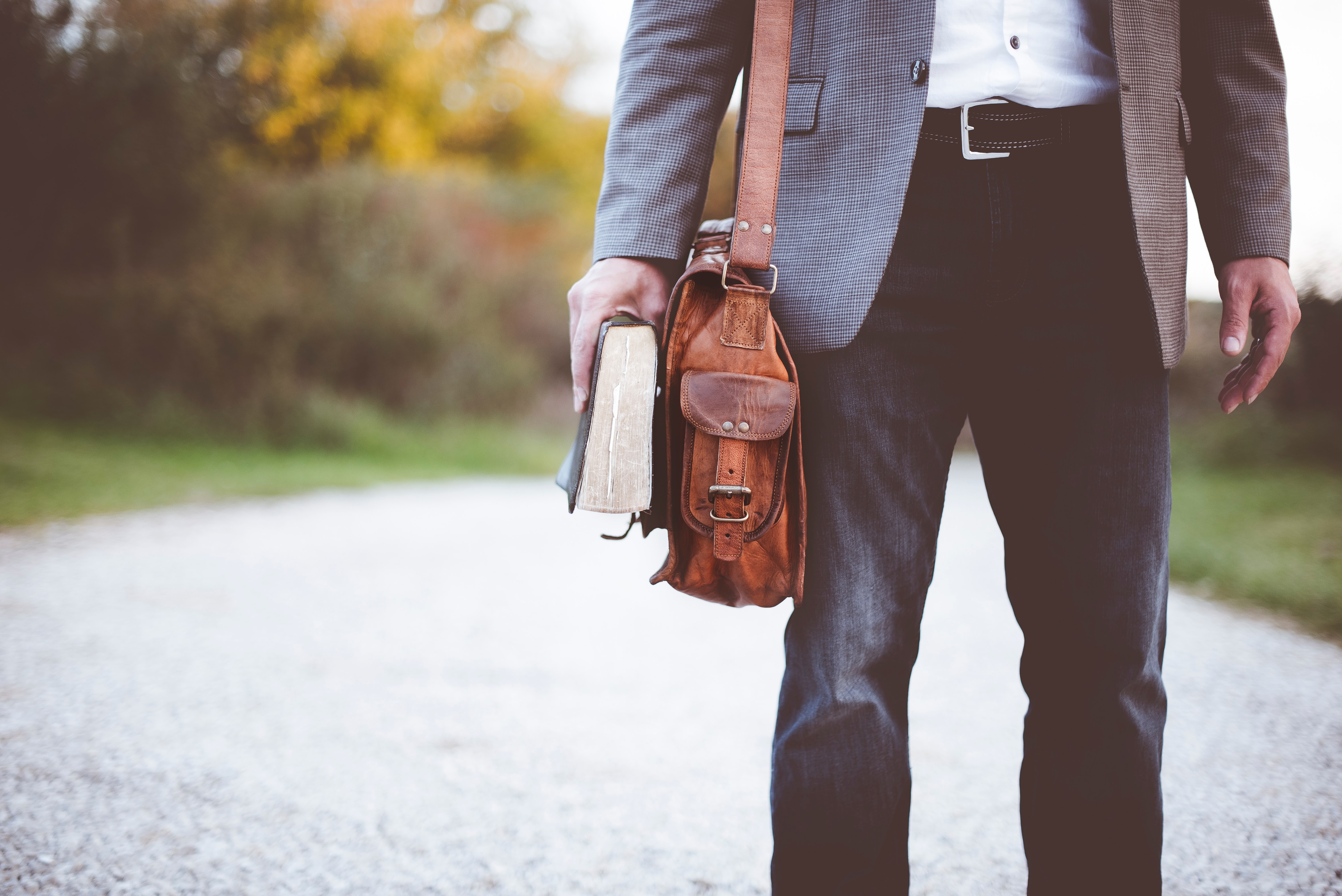 Man with leather bag and book; image by Ben White, via Unsplash.com.