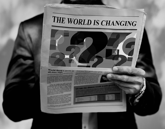 Black and white image of a man reading a newspaper.