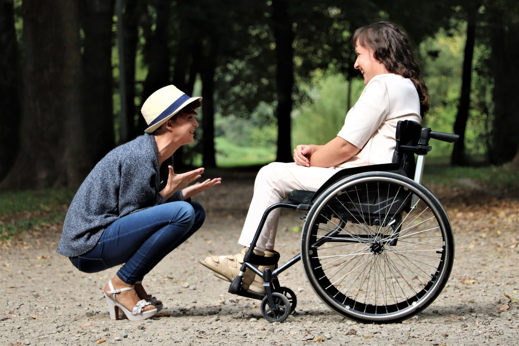 Woman seated in wheelchair facing woman in hat; image by Judita Tamošiūnaitė, via Pexels.com.