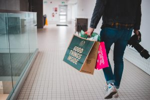 Man with shopping bags and camera; image by Erik Mclean, via Unsplash.com.