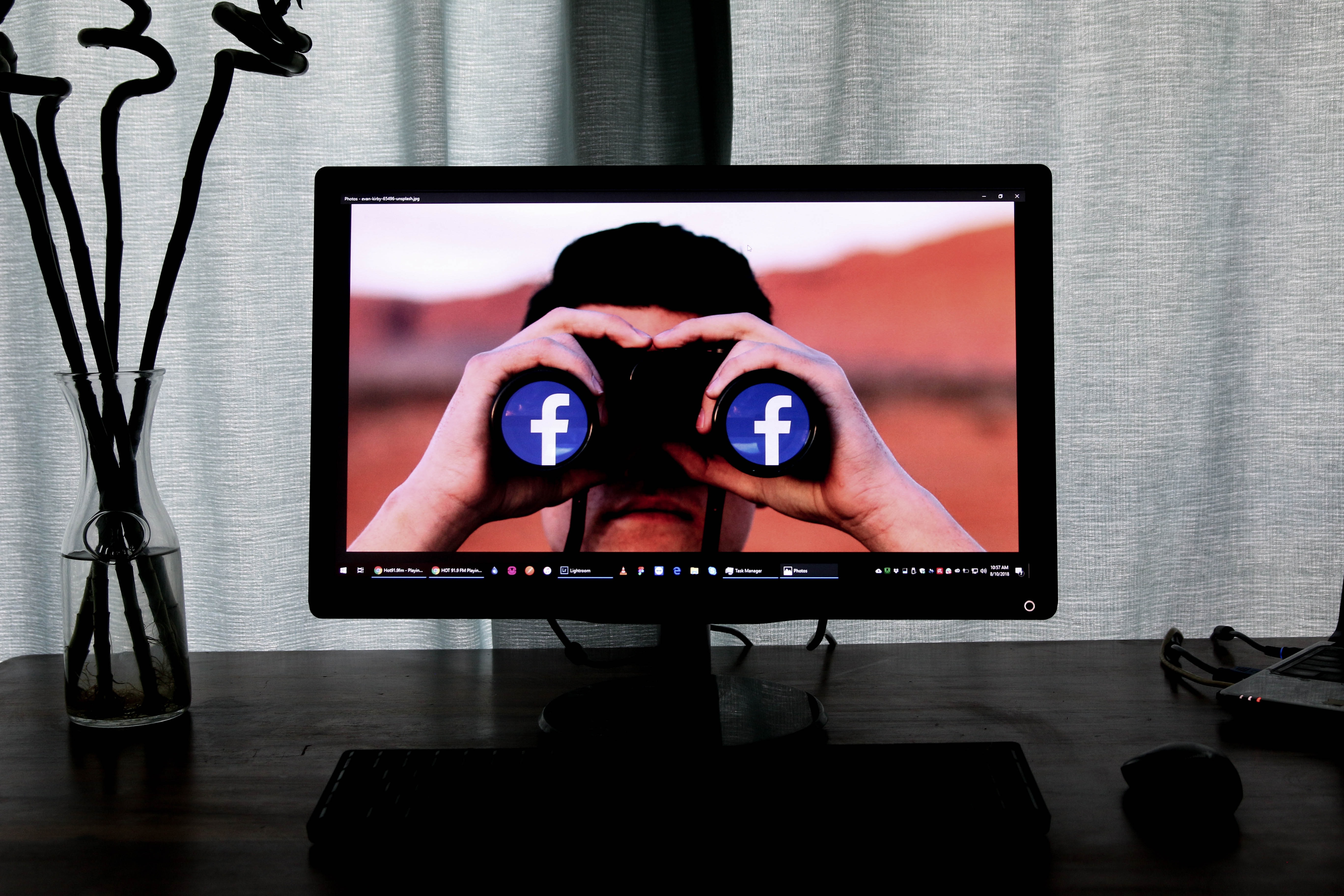Computer monitor showing man with binoculars staring out at viewer. Lenses of binoculars are the Facebook logo. Image by Glen Carrie, via Unsplash.com.