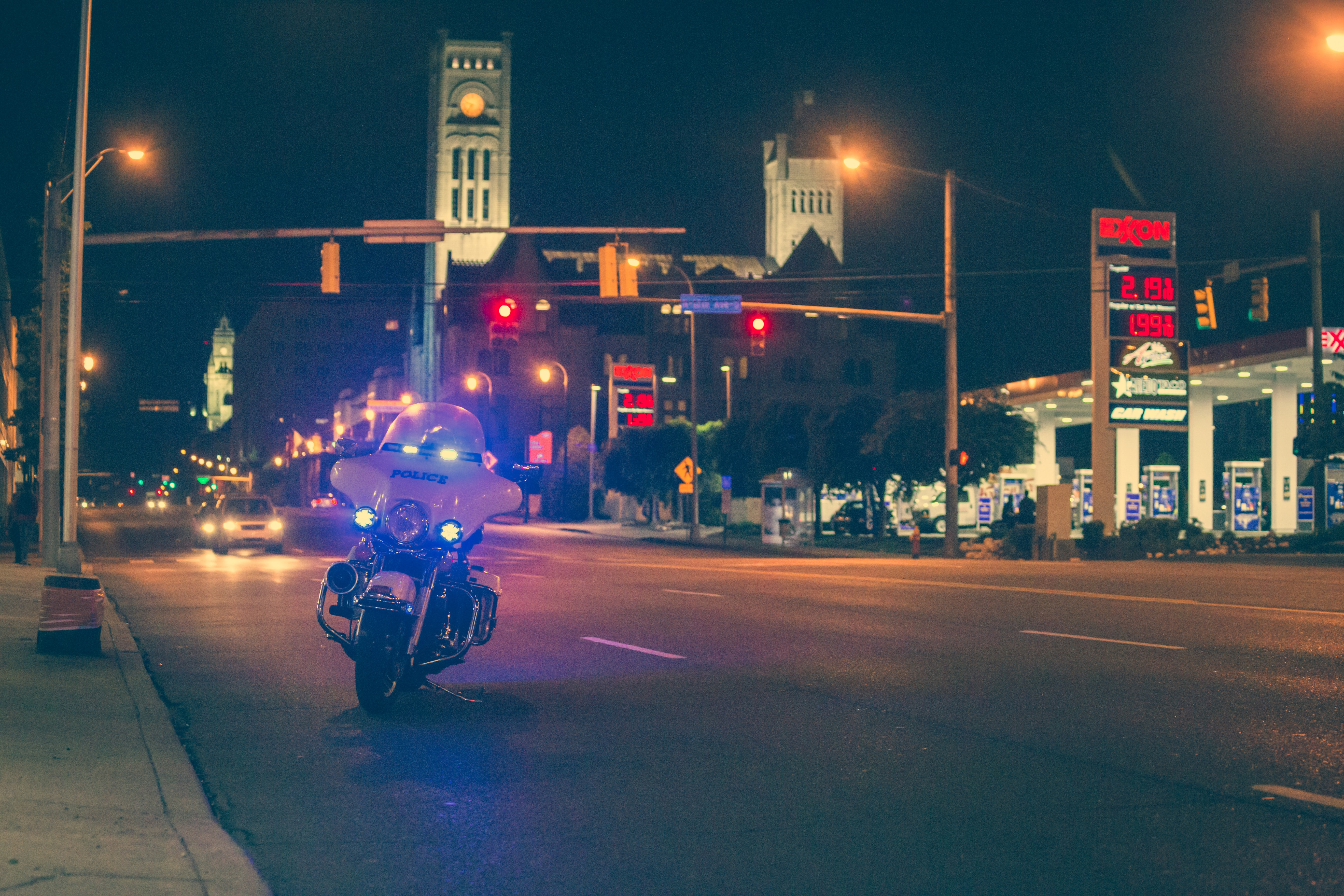 Police motorcycle with lights on parked at side of road at night; image by JP Valery, via Unsplash.com.