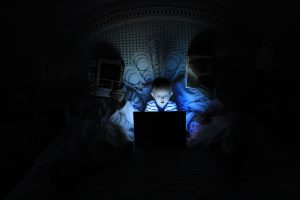 Family in bed, parents reading and child on laptop; image by Ludovic Toinel, via Unsplash.com.