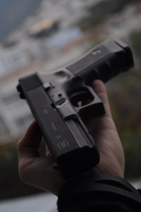 Man with black semi-automatic pistol in palm of hand; image by Roman Poberezhnik, via Unsplash.com.
