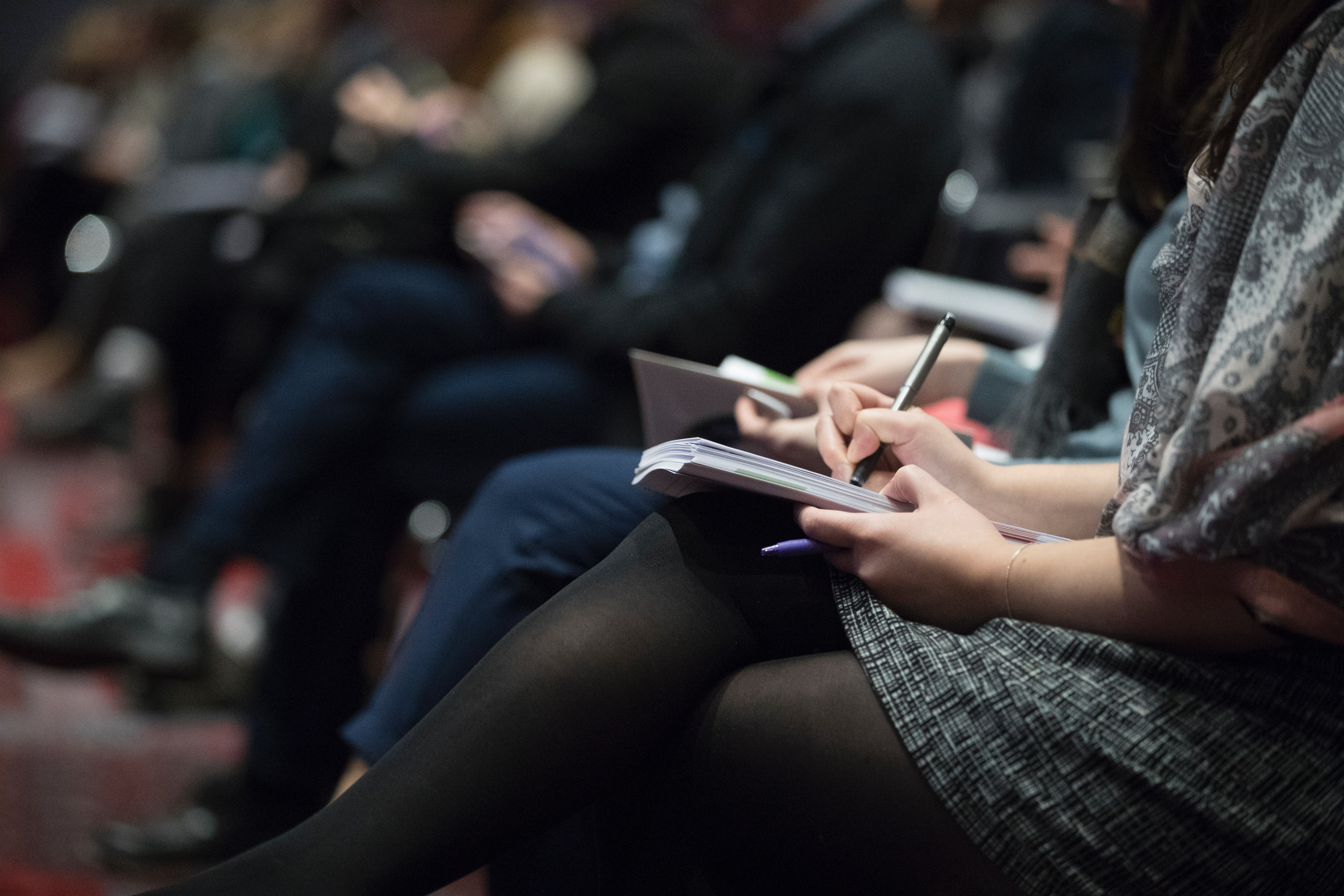Woman writing in notebook with pen, seated in full auditorium; image by The Climate Reality Project, via Unsplash.com.