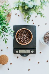 Bowl filled with coffee beans on black digital scale at 39 grams; image by Tyler Nix, via Unsplash.com.