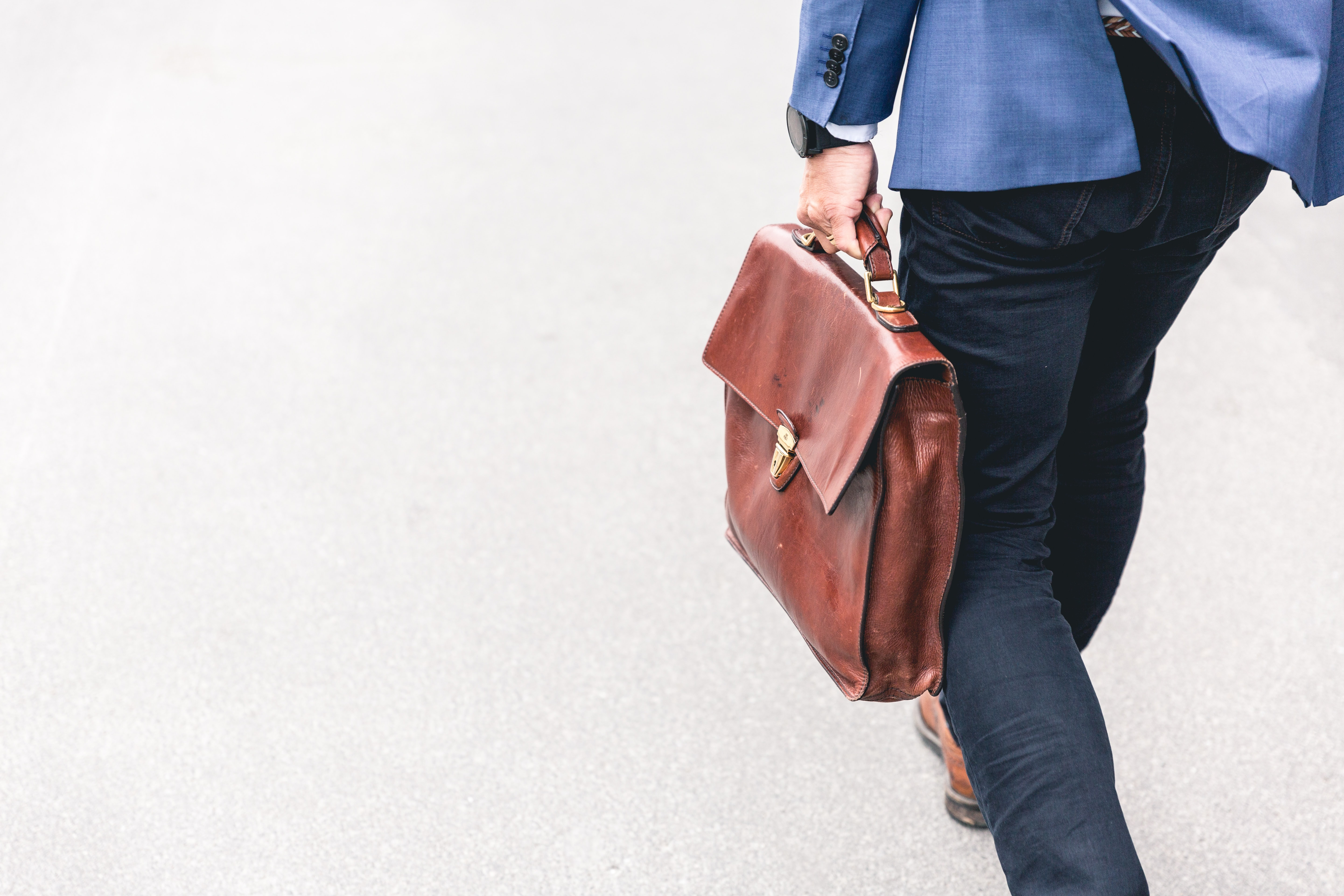 Man walking with brown leather briefcase; image by Marten Bjork, via Unsplash.com.