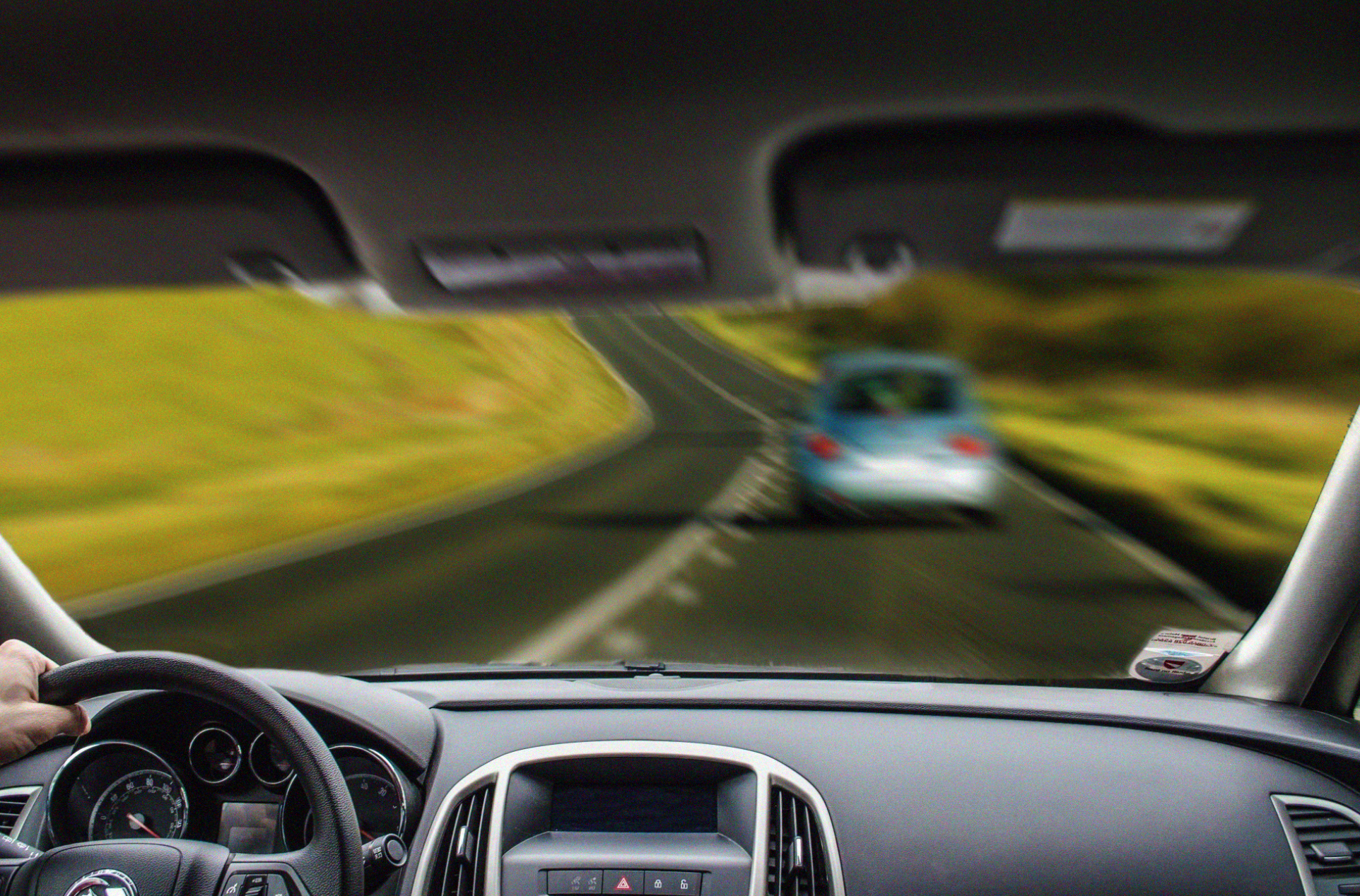 Man driving, in-focus view of dash with out-of-focus view of car ahead; image by JoeNomi 1961, via Wikimedia Commons, CC0.