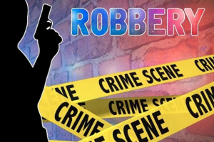 "Graphic of man with gun, crime scene tape, and the word ""Robbery"" against a brick wall; graphic by 1800420Laws, via Pixabay.com."