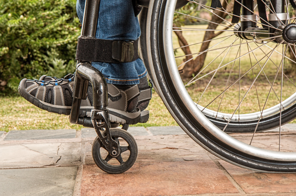 Close up photo of person's feet as they sit in a wheelchair; image by Stevepb, via Pixabay.com.