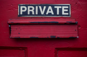"""Red door with mail slot and sign saying """"Private."""" Image by Dayne Topkin, via Unsplash.com."""