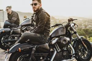 Two men sitting on parked motorcycles; image by Harley-Davidson, via Unsplash.com.