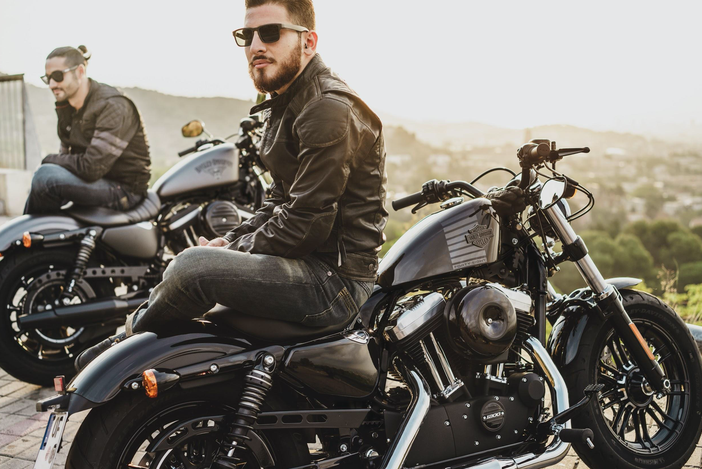 Two men sitting on parked motorcycles; image by Harley-Davidson, via Unsplash.com.