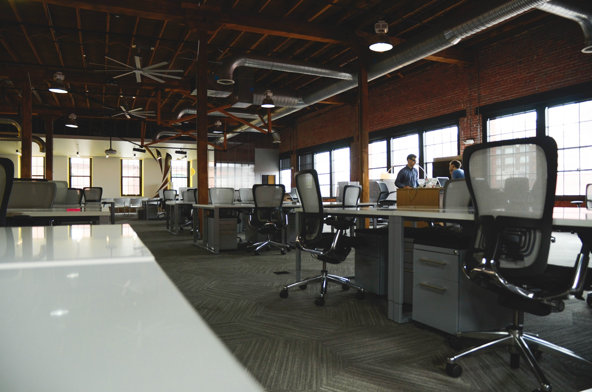 Open room full of workstations; image by Startup Stock Photos, via Pexels.com.