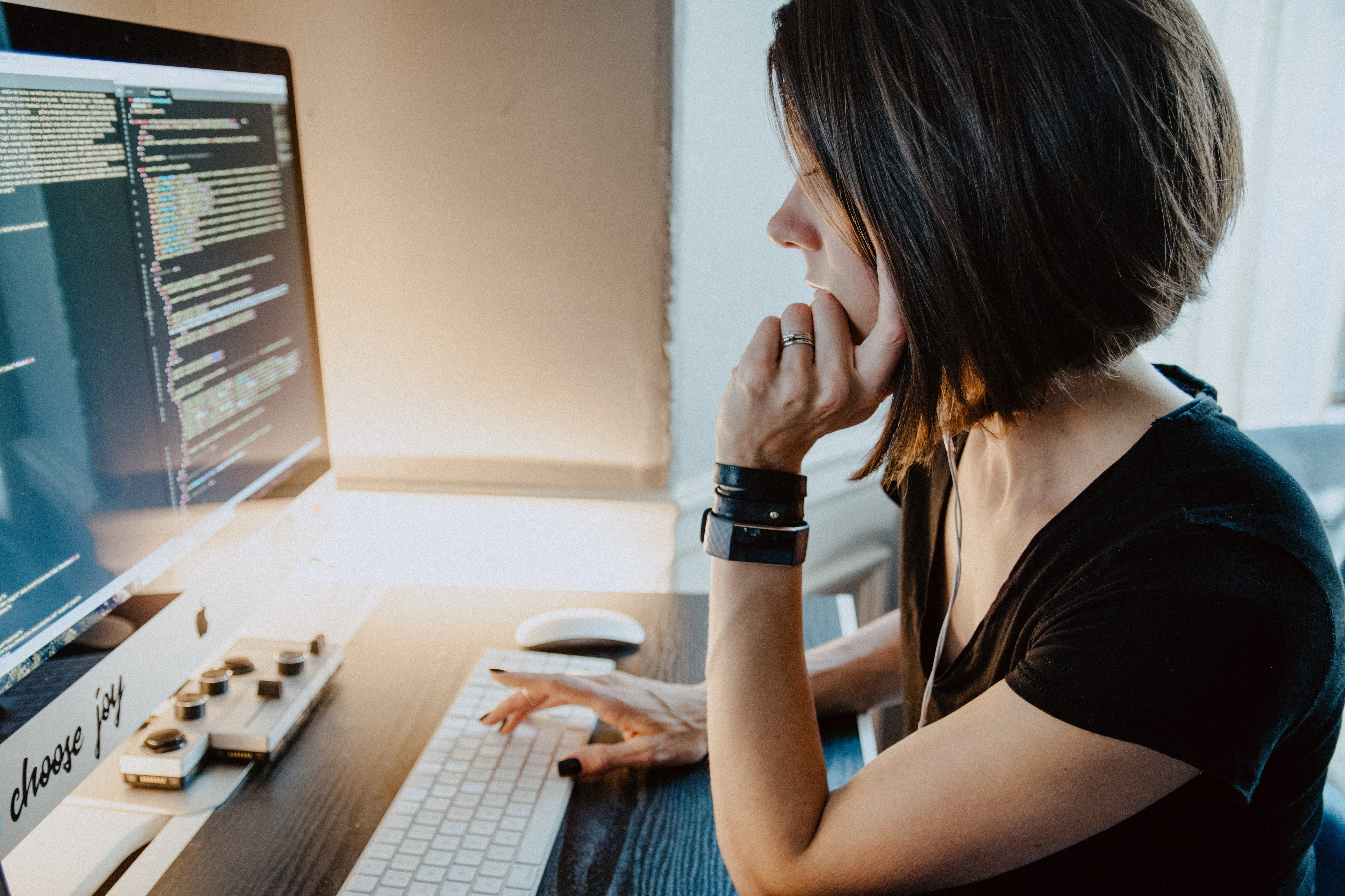 Woman sitting at a desk in front of coding computer screen; image by Kelly Sikkema, via Unsplash.com.