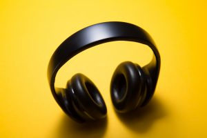 Wireless headphones with yellow background; image by Malte Wingen, via Unsplash.com.