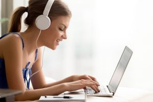 Side view portrait of smiling young woman in headphones typing on laptop; image by yanalya, via Freepik.com.