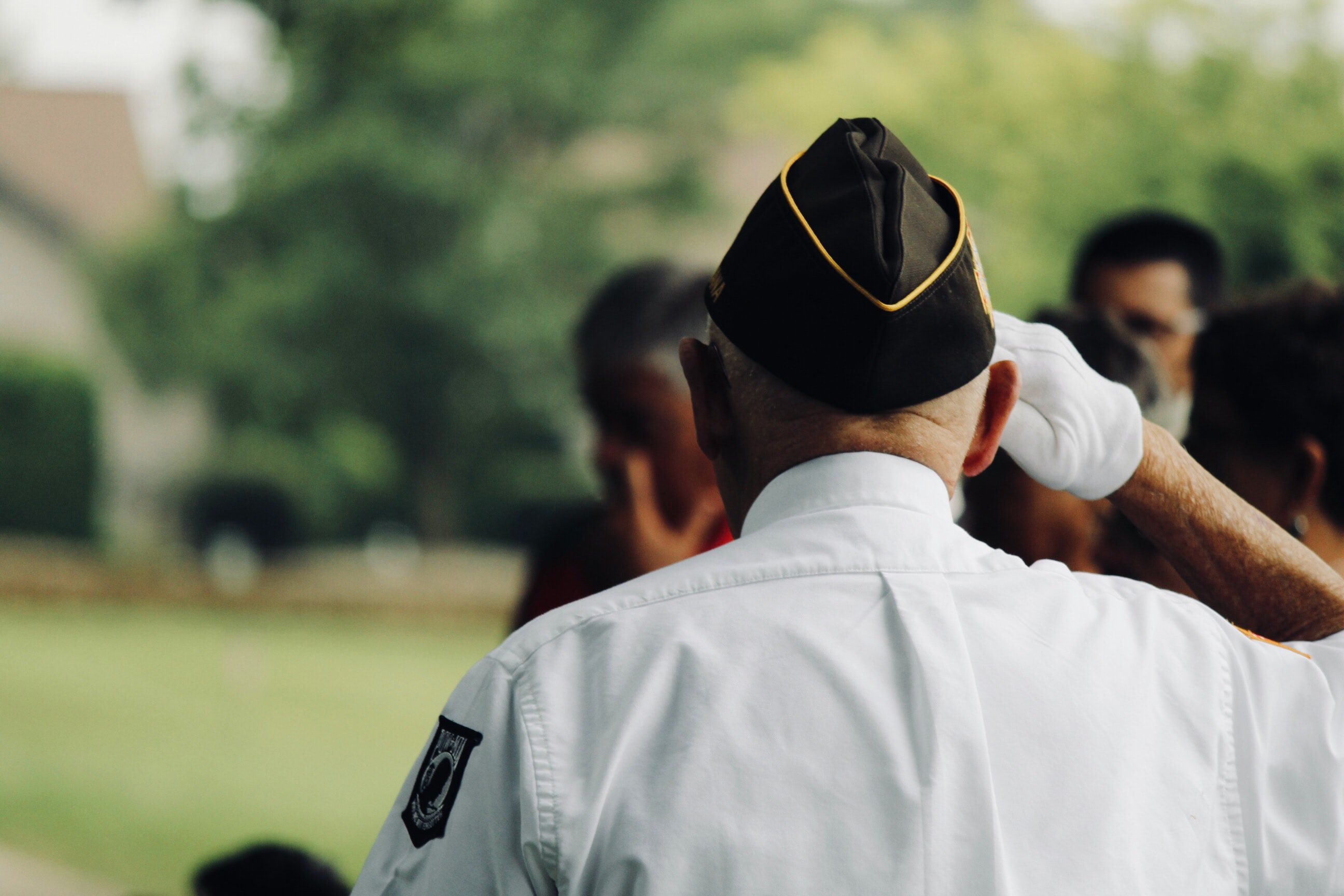 Back view of veteran saluting; image by Sydney Rae, via Unsplash.com.