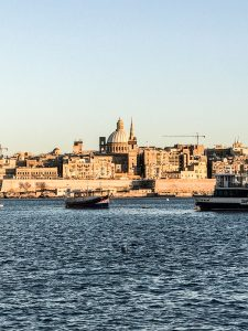Two ships on the water in front of the beautiful architecture of Valletta, Malta; image by Ines Bahr, via Pexels.com.