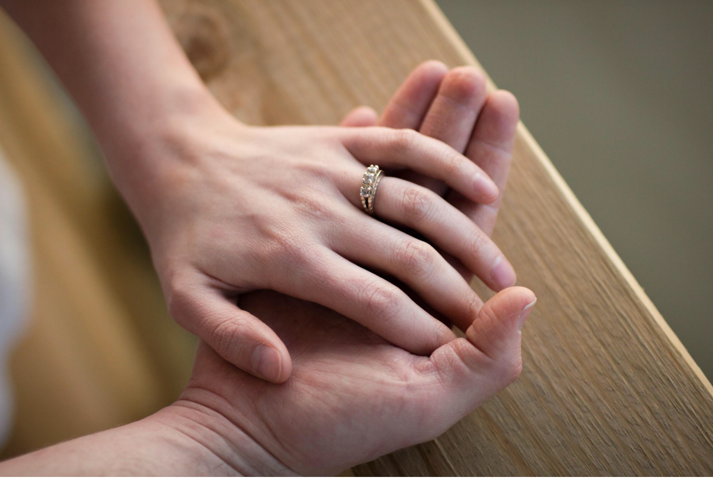 Man and woman wearing wedding ring holding hands; image by Rachel Crowe, via Unsplash.com.