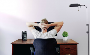 Man sitting at desk with hands clasped behind his head; image by Jason Strull, via Unsplash.com.