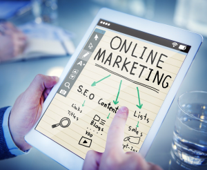 """Man holding a tablet with """"Online Marketing"""" on the screen; image by muneebfarman, via Pixabay.com."""