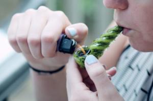 Woman lighting marijuana in pipe; image by Sharon McCutcheon via Unsplash.com.