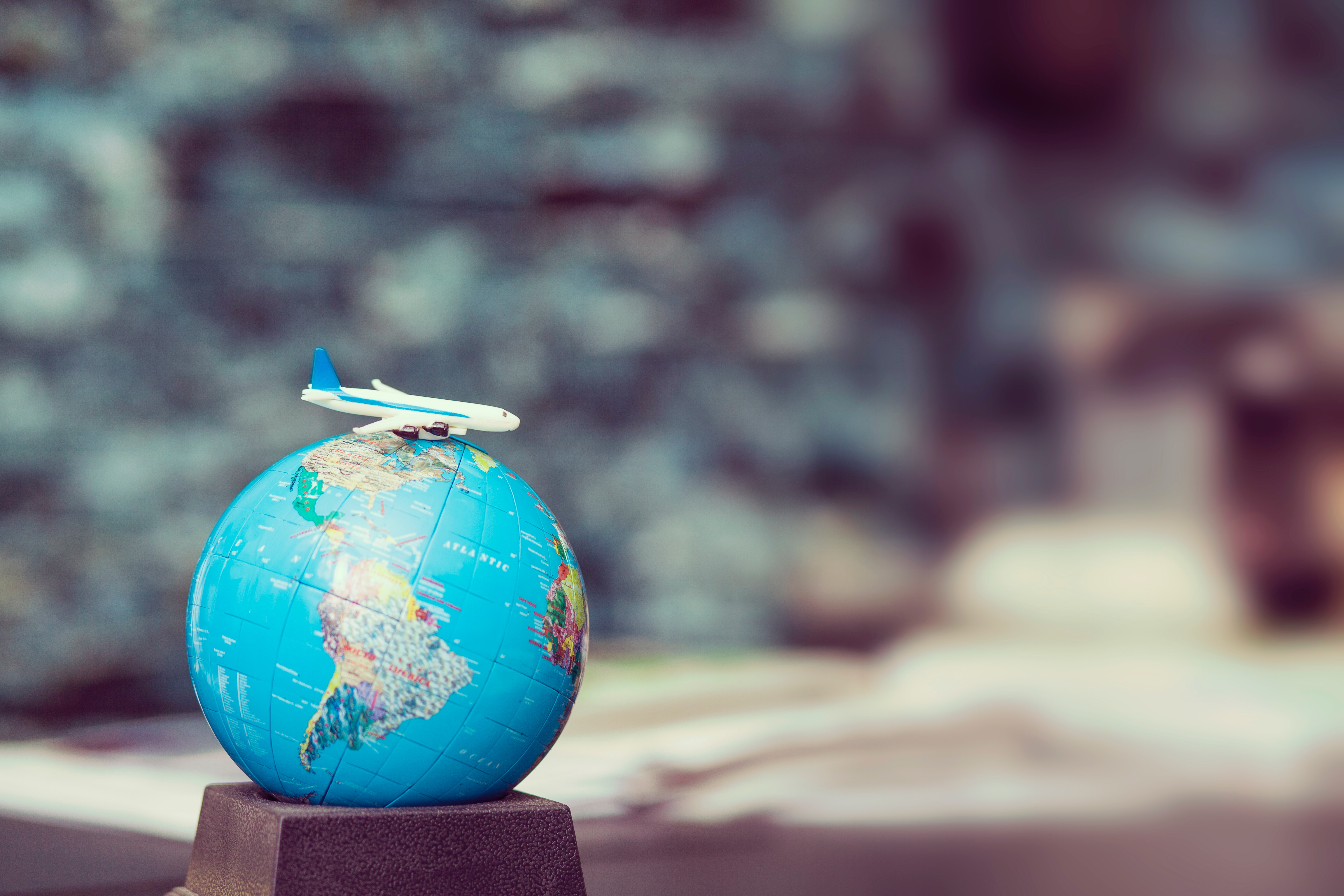 Toy plane on top of globe; image by Frank Vessia, via Unsplash.com.
