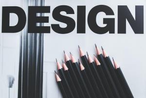 "Black pencils on light background with ""DESIGN"" written above; image by kaboompics.com, via Pixabay.com."