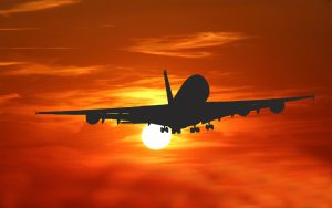 The silhouette of a commercial aircraft backed by a vivid sunset.