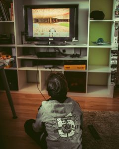 Boy sitting on floor near TV, playing video game; image by Albert Renn, via Unsplash.com.