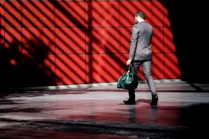 Man in suit carrying green bag and walking in front of red wall; image by Clem Onojeghuo, via Unsplash.com.
