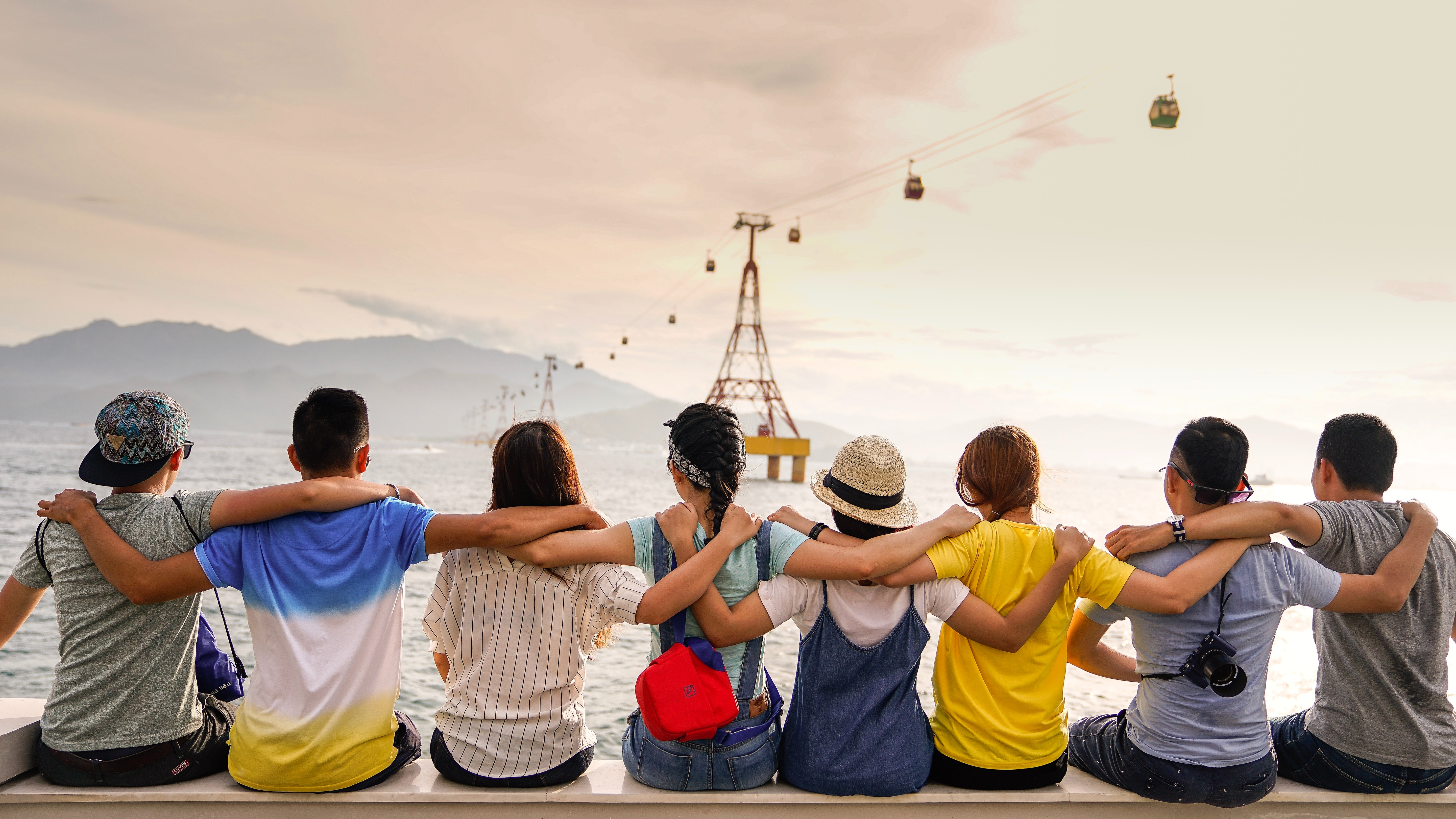 Group of people sitting on bench with arms around each other looking at water; image by Duy Pham, via Unsplash.com.
