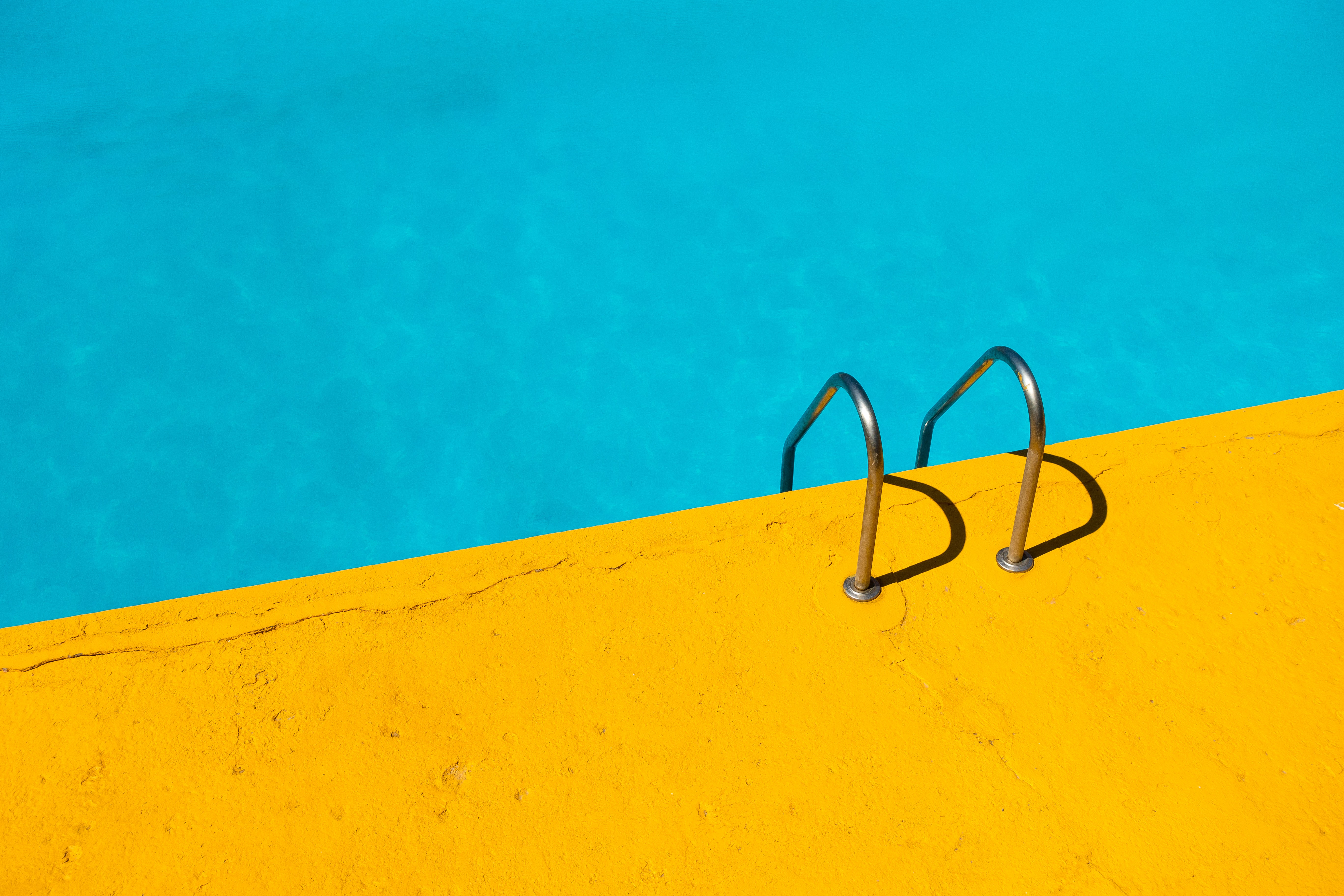 Swimming pool with ladder and yellow border; image by Etienne Girardet, via Unsplash.com.