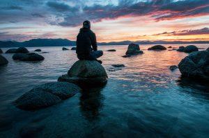 Man sitting on rock in body of water; image by Keegan Houser, via Unsplash.com.