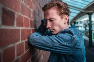 Teen boy in denim jacket leaning on brick building; image by Peter F. Wolf, via Unsplash.com.